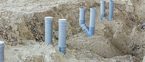 Set of waste pipes are assembled and lined up on building site.